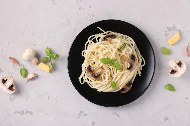 Spaghetti met champignons en basilicum op zwarte plaat op grijze achtergrond