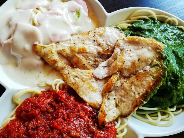 Spaghetti met drie sauzen van verschillende smaken en gegrilde kip