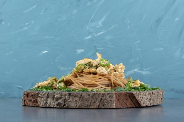 Spaghetti met gebakken ei op stuk hout