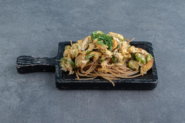 Spaghetti met gebakken ei op zwart bord