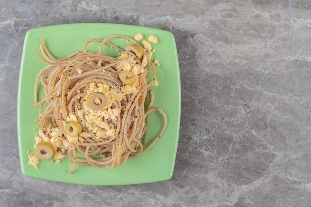Spaghetti met gebakken eieren op groene plaat.