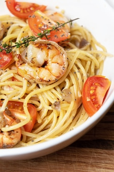 Spaghetti met gebakken garnalen en verse tomaten.