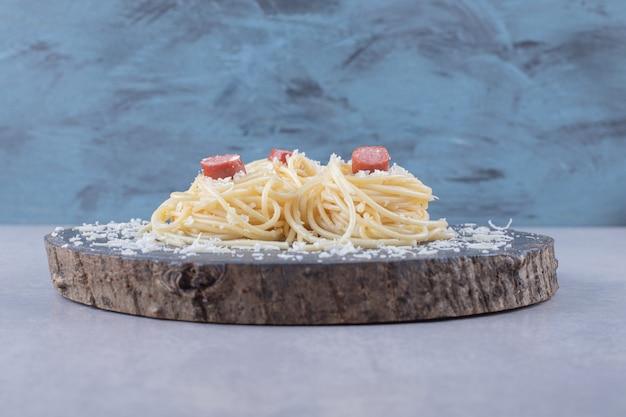 Spaghetti met gebakken worstjes op een stuk hout.