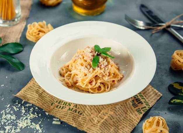 Spaghetti met gehakte parmezaanse kaas en groene muntblaadjes.
