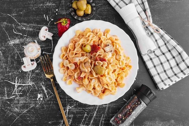 Spaghetti met gemengde ingrediënten in een witte plaat, bovenaanzicht.