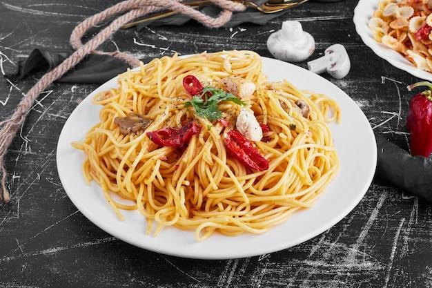 Spaghetti met gemengde ingrediënten in een witte plaat.