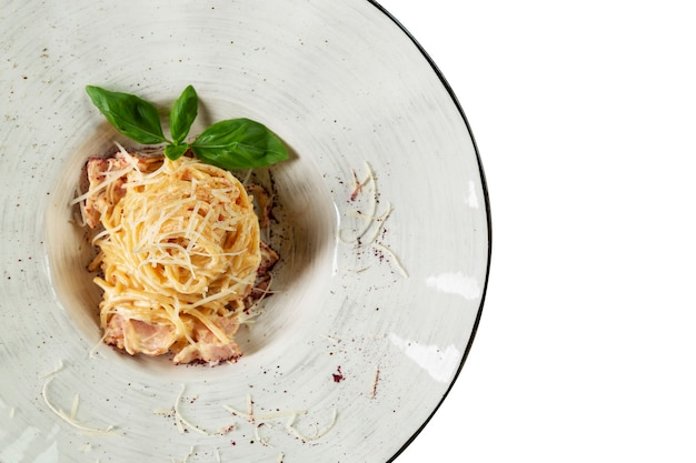 Spaghetti met ham en kaas in een bord. een traditioneel italiaans gerecht om van te watertanden. bovenaanzicht. geïsoleerd op een witte achtergrond. ruimte voor tekst.