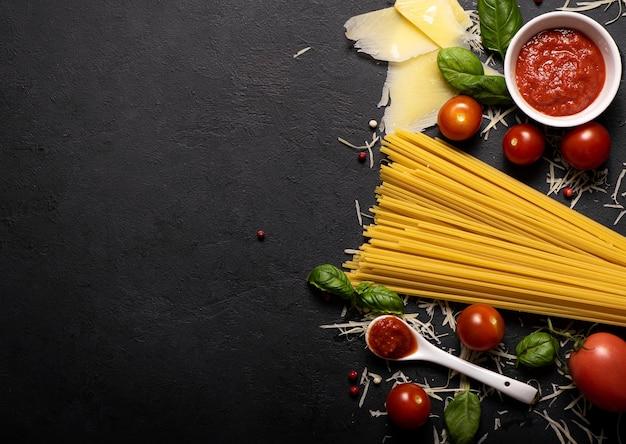 Spaghetti met parmezaanse kaas, basilicum en tomatensaus op een zwarte achtergrond, platte ley