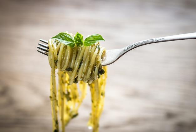 Spaghetti met pestosaus en basilicumblad op de vork