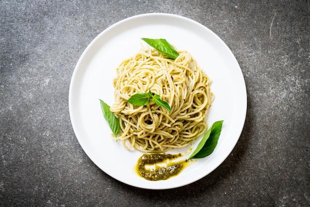 Spaghetti met pestosaus, olijfolie en basilicumblaadjes.