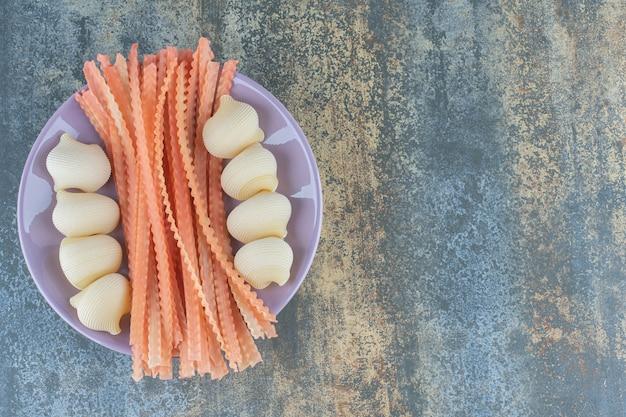 Spaghetti met pijppasta's in de kom, op het marmeren oppervlak.