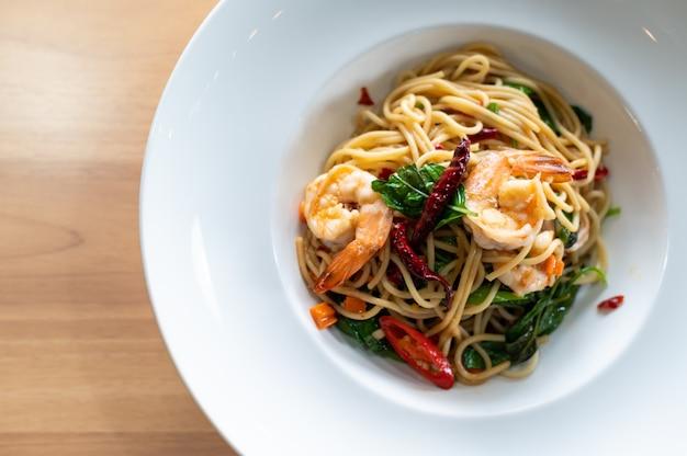 Spaghetti met pittige garnalen op houten tafel