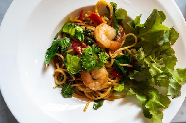 Spaghetti met pittige gemengde garnalen en groenten in witte schotel