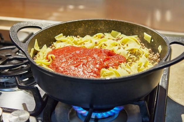 Spaghetti met rundergehakt en saus, gebakken in pan voor het maken van spaghetti bolognese volgens recept van internet.