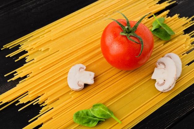 Spaghetti met tomaat, champignons en spinazie op zwarte achtergrond. bovenaanzicht. gezond eten concept. bereiding van producten.