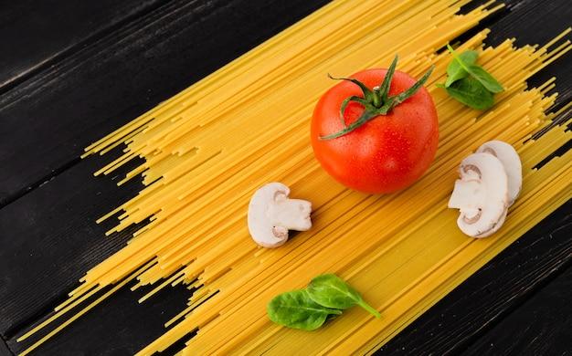 Spaghetti met tomaat, champignons en spinazie op zwarte achtergrond. gezond eten concept.