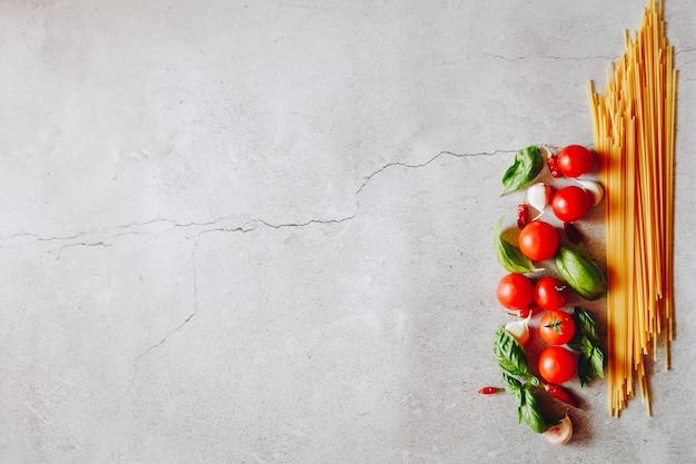 Spaghetti met tomaten en knoflook op een betonnen tafel