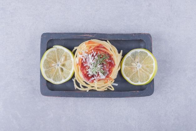 Spaghetti met tomatenpasta en citroenen op donkere plaat.