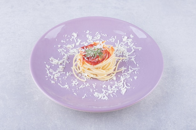 Spaghetti met tomatenpasta op paarse plaat.