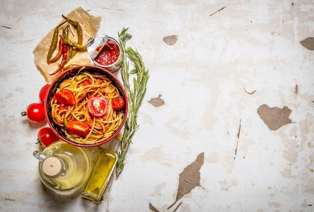 Spaghetti met tomatenpuree, hete spaanse peperpeper en olijfolie op rustieke achtergrond