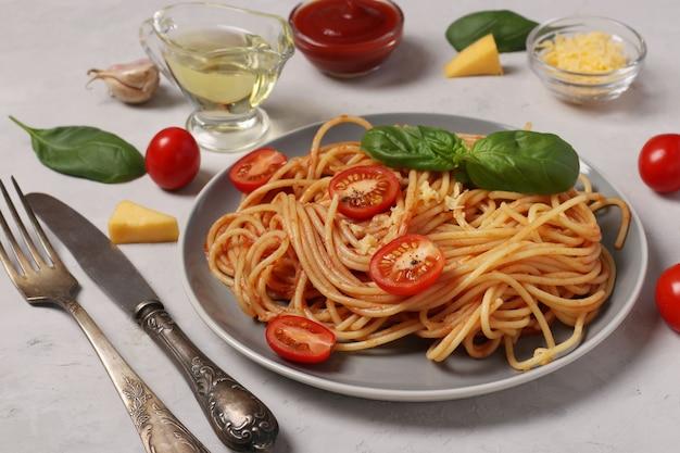 Spaghetti met tomatensaus en kerstomaatjes met basilicum op grijze plaat op lichte ondergrond, close-up