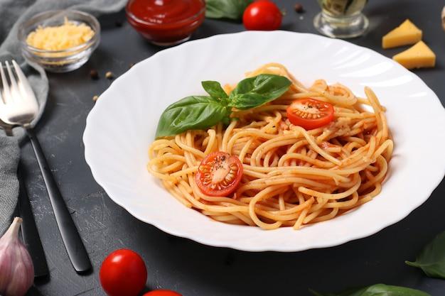 Spaghetti met tomatensaus en kerstomaatjes met basilicum op witte plaat op donkere achtergrond. detailopname
