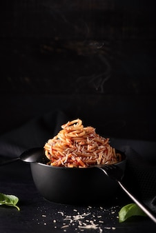 Spaghetti met tomatensaus en parmezaanse kaas in zwarte kom