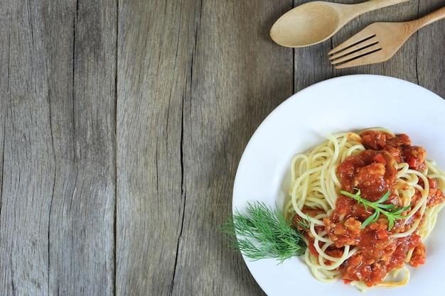 Spaghetti met tomatensaus in een witte schotel op houten vloer achtergrond