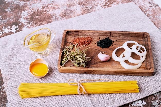 Spaghetti met verse kruiden op bruine lijst.