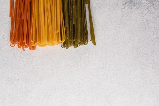 Spaghetti noedels. pasta achtergrond. spinazie, tomaat en klassieke spaghetti op witte stenen achtergrond met kopie ruimte.