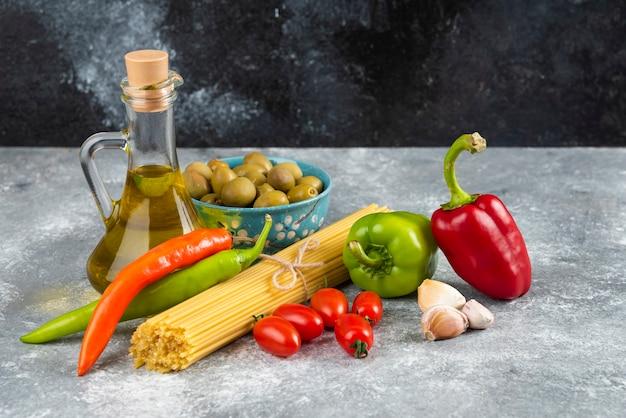 Spaghetti, olie en diverse groenten op stenen tafel.