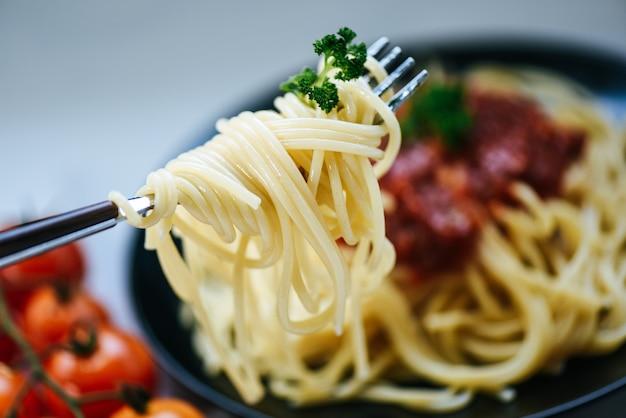 Spaghetti op vork en spaghetti bolognese italiaanse deegwaren met peterselie in het restaurant italiaanse voedsel en het menu