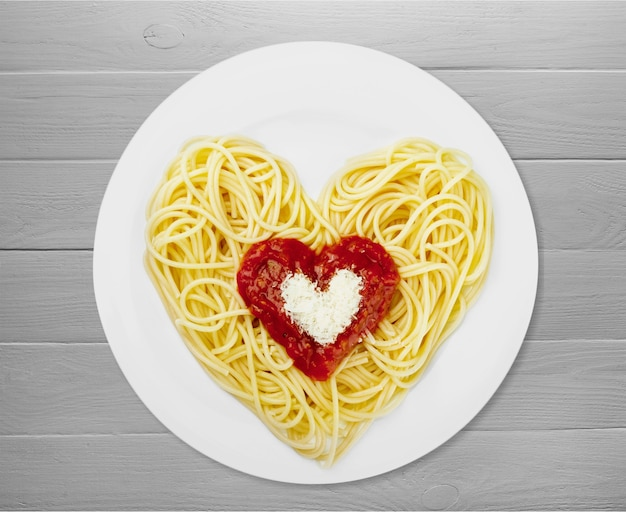 Spaghetti pasta in hartvorm op tafel.
