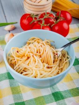 Spaghetti pasta met chili vlokken in een witte kom met vork en verse tomaten op een tafellaken