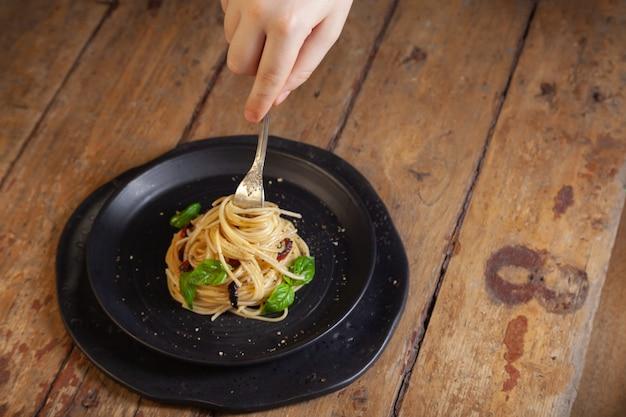 Spaghetti pasta met groenten, peper, basilicum bladeren op zwarte ronde plaat op bruin rustieke vintage houten achtergrond
