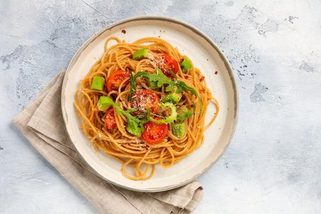 Spaghetti pasta met pesto, avocado en tomaten in rustieke witte plaat. rauw veganistisch voedselconcept. bovenaanzicht.