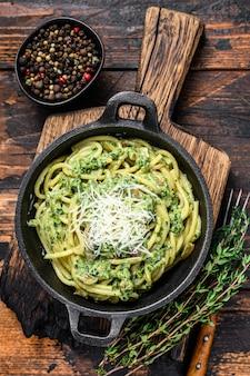 Spaghetti pasta met pestosaus, spinazie en parmezaan in een pan. donkere houten achtergrond. bovenaanzicht.