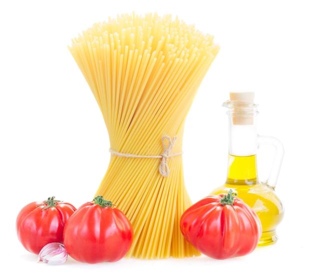 Spaghetti pasta met rauwe tomaten en olijfolie geïsoleerd op wit
