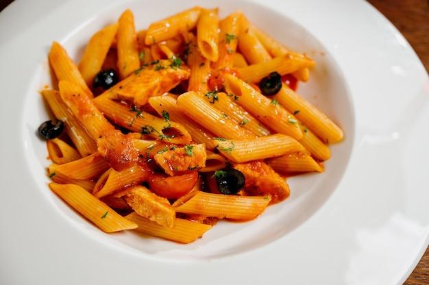 Spaghetti pasta met tomaten en peterselie op houten tafel