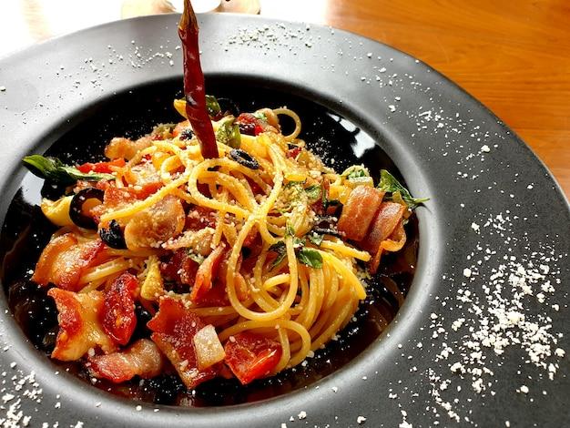 Spaghetti pittige droge chill knoflook met spek en parmezaanse kaas in zwarte plaat
