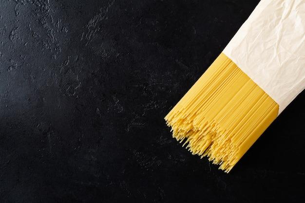 Spaghetti rauwe pasta in een papieren zak op een zwarte betonnen tafel. koken concept. bovenaanzicht met kopie ruimte.