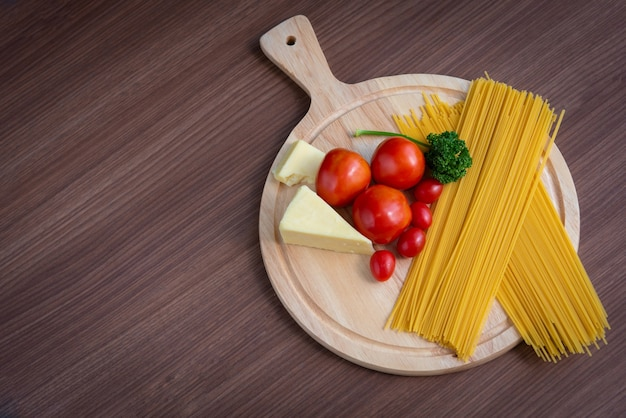 Spaghetti, tomaten, broccoli en boter op een bruine houten vloer