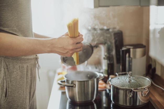 Spaghetti van mensen de kokende deegwaren thuis in de keuken. thuis koken of italiaans koken concept.