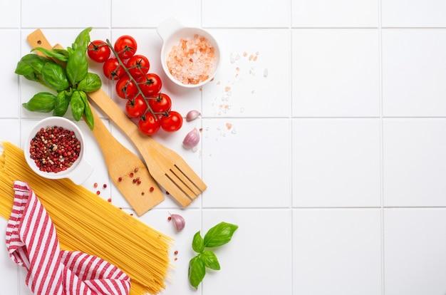 Spaghetti, verse tomaat, kruiden en specerijen. samenstelling van gezonde voedselingrediënten geïsoleerd op een witte achtergrond, bovenaanzicht. bespotten.
