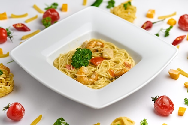 Spaghetti zeevruchten pasta met garnalen garnalen en tomaten bovenaanzicht op witte achtergrond