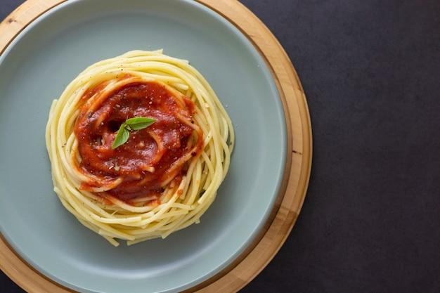 Spaghettideegwaren met tomatensaus en basilicum in plaat op dark. pasta plaat geïsoleerd. bovenaanzicht met copyspace.