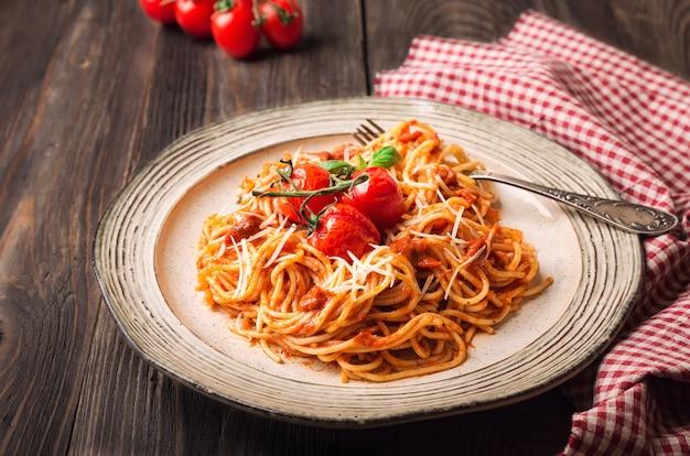 Spaghettideegwaren met tomatensaus en gebakken tomatenkers op rustieke houten