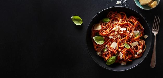 Spaghettideegwaren met tomatensaus, kaas en basilicum die in kom wordt gediend. horizontaal