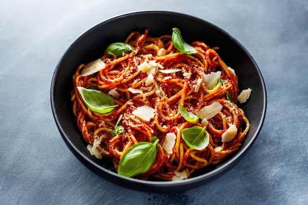 Spaghettideegwaren met tomatensaus, kaas en basilicum die in kom wordt gediend