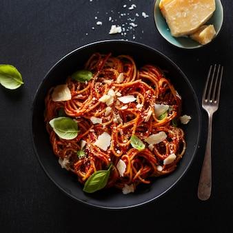 Spaghettideegwaren met tomatensaus, kaas en basilicum die in kom wordt gediend.